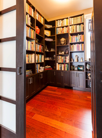 The owners chose to have a small library with shoji screen entry, rather than a large walk-in closet. Photograph by: Debra Brash