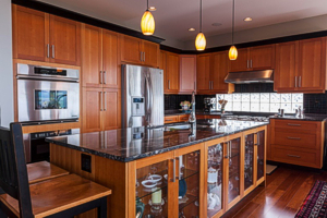 "The kitchen island is a handsome china cabinet. Above it are delicate pendant lights. ""It doesn't matter how beautiful a home is, if you don't have good lighting, it won't look great,"" said designer Wendy Wilson, who used recessed lighting, wall sconces, pendants and multi-level lighting to set the mood. Photograph by: Debra Brash"