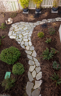 A stone path leads through the easy-care garden. Photograph by: Debra Brash