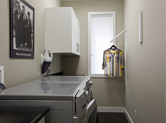 Handy wall attachments flip down for extra hanging space in the laundry room. Photograph by: Debra Brash